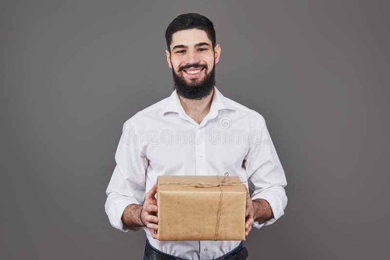 Z miłością dla ciebie Dobry przyglądający młody człowiek trzyma prezenta pudełko i patrzeje kamerę w niebiescy dżinsy koszula pod zdjęcia royalty free