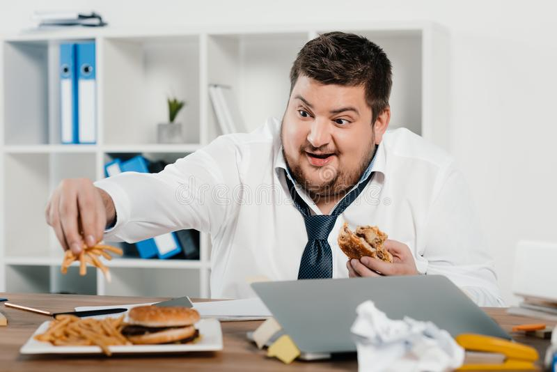 z nadwagą biznesmena łasowania hamburgery i francuzów dłoniaki zdjęcia stock
