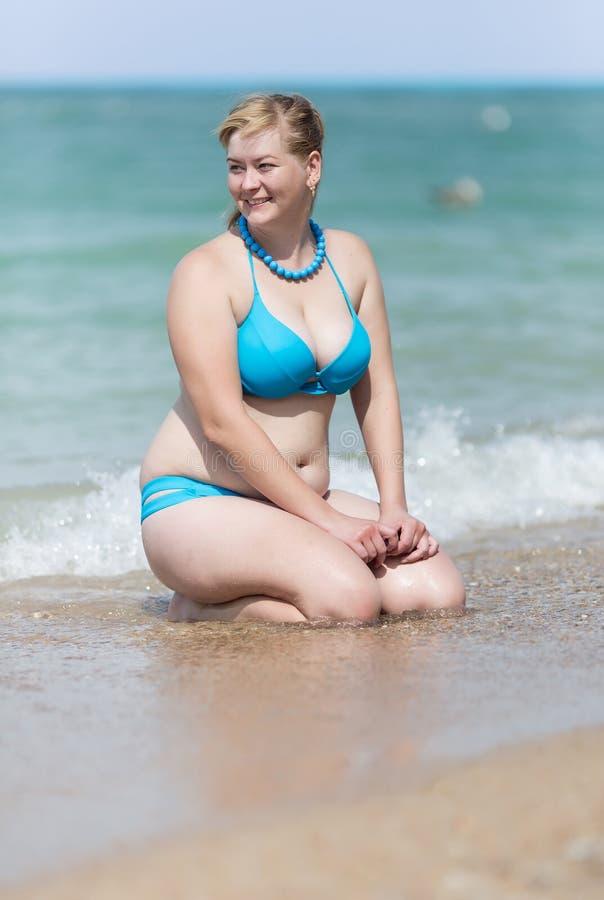 Z nadwagą blondynka w bikini obsiadaniu wewnątrz nawadnia krawędź zdjęcie royalty free