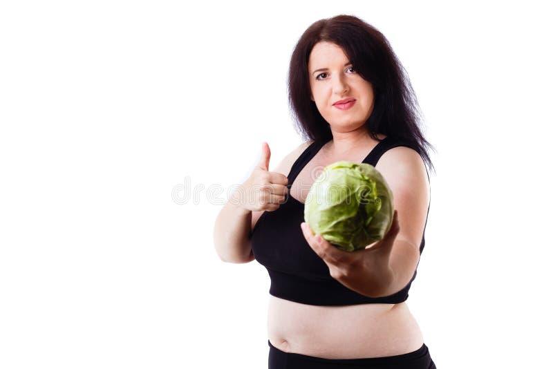 Z nadwagą kobieta z kapustą i kciuk up gestykulujemy obraz stock