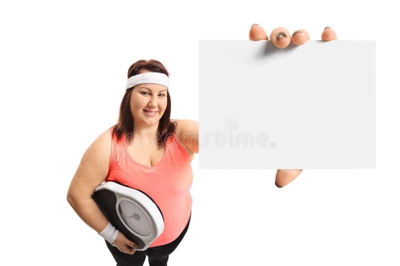 Z nadwagą kobieta trzyma ciężar skala i pustą kartę zdjęcie stock