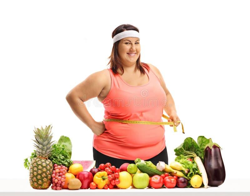 Z nadwagą kobieta trzyma pomiarowej taśmy wokoło jej talii obrazy stock