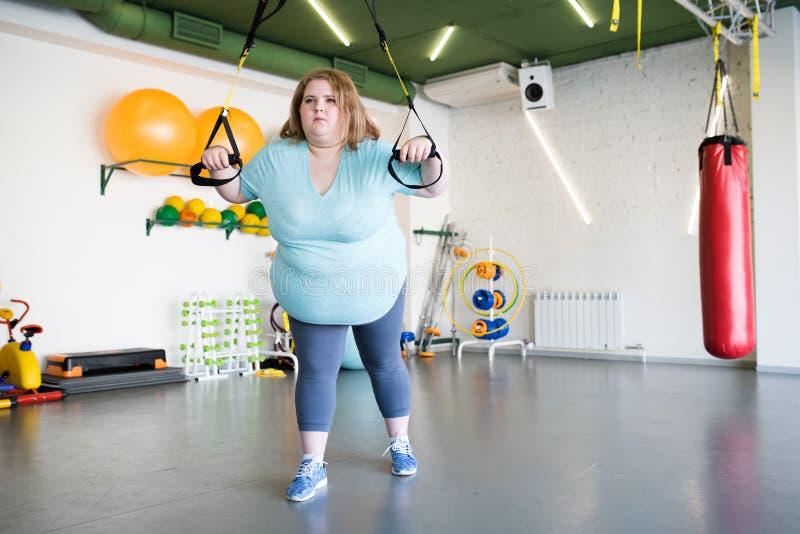 Z nadwagą kobieta Używa maszyny w Gym obrazy stock