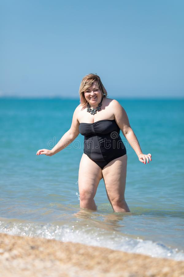 Z nadwagą kobieta w czarnym stroju jednoczęściowy swimsuit przy morzem obraz royalty free