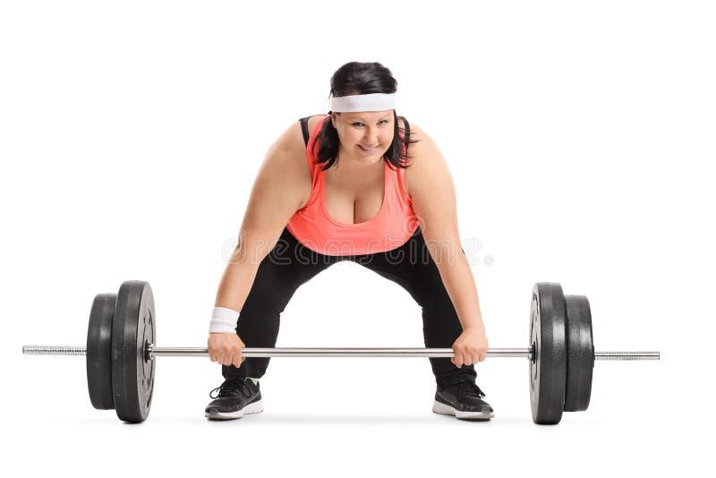 Z nadwagą kobiety narządzanie podnosić barbell zdjęcia stock