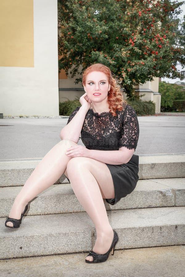 Z nadwagą kobiety obsiadanie ubierał w czerni na schody fotografia royalty free