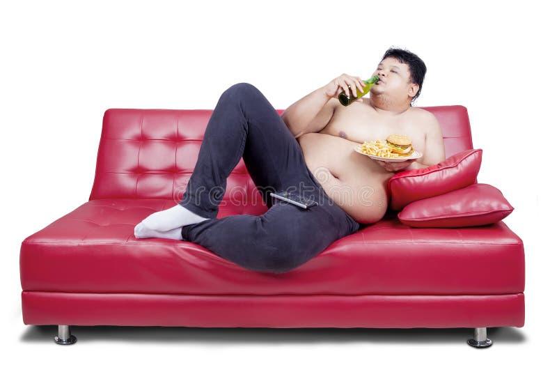 Z nadwagą mężczyzna opiera na leżance obraz stock