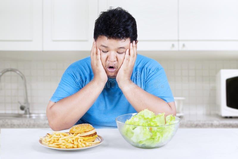Z nadwagą osoba z dwa rodzajami jedzenie 1 obrazy stock