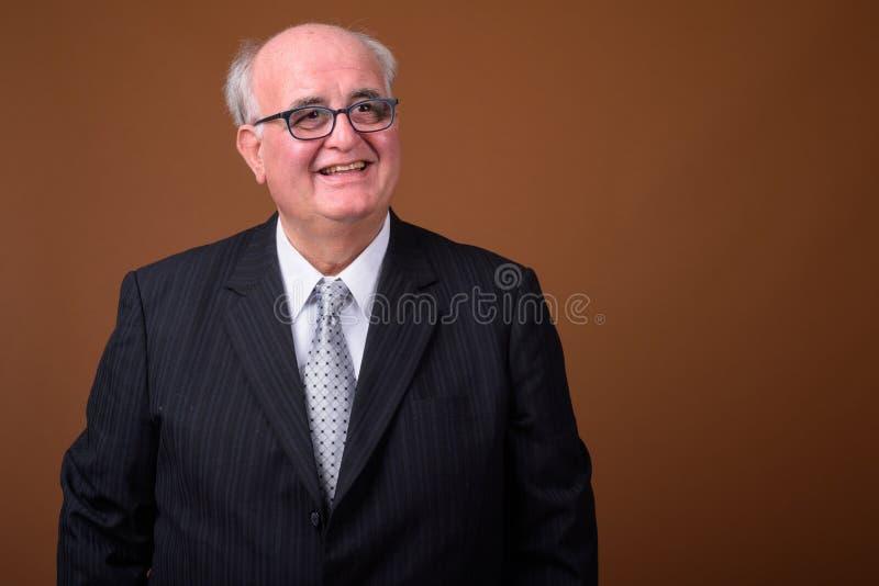 Z nadwagą starszy biznesmen jest ubranym eyeglasses przeciw brown b obraz stock