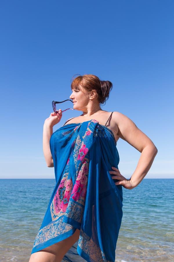 Z nadwagą w średnim wieku kobieta przy morzem obraz stock