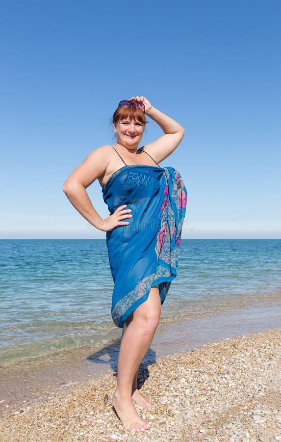 Z nadwagą w średnim wieku kobieta przy morzem zdjęcia stock