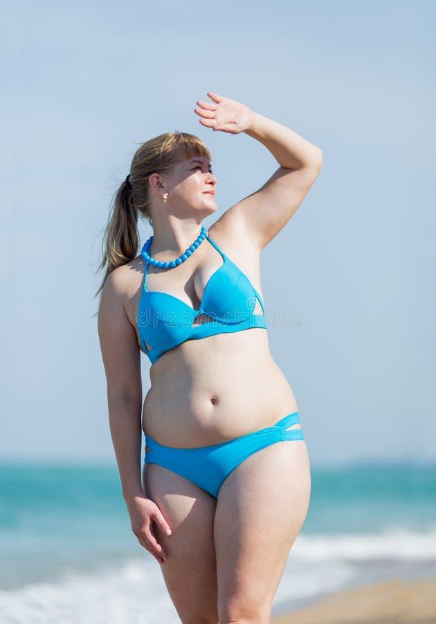 Z nadwagą w średnim wieku kobieta w błękitnym bikini przy morzem obraz royalty free