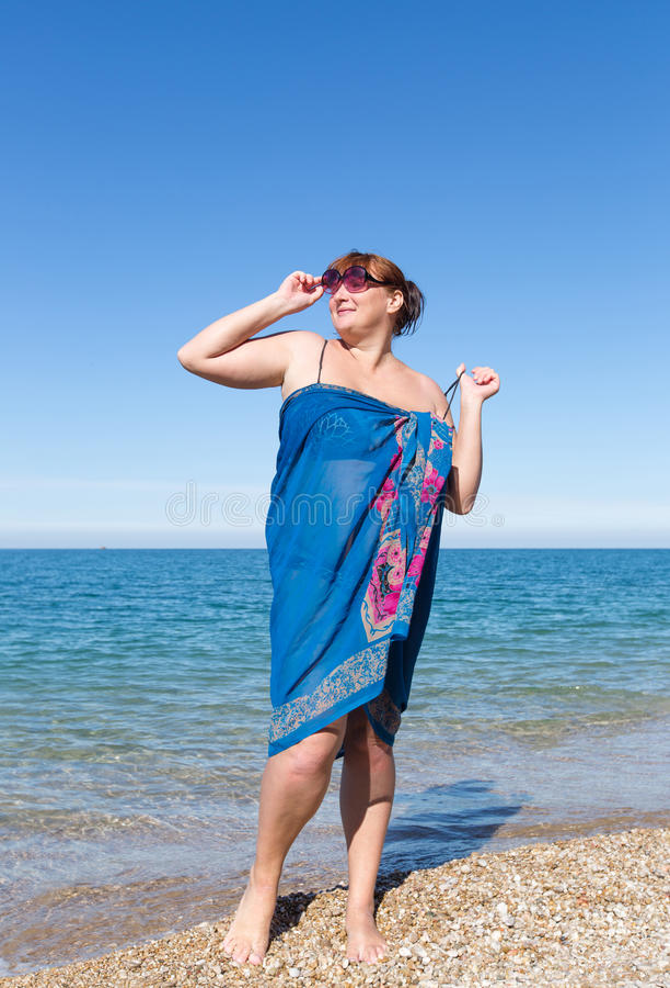 Z nadwagą w średnim wieku kobieta w pareo przeciw morzu zdjęcia stock