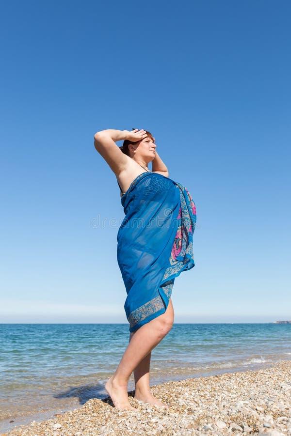 Z nadwagą w średnim wieku kobieta zawijająca w pareo przy morzem fotografia stock
