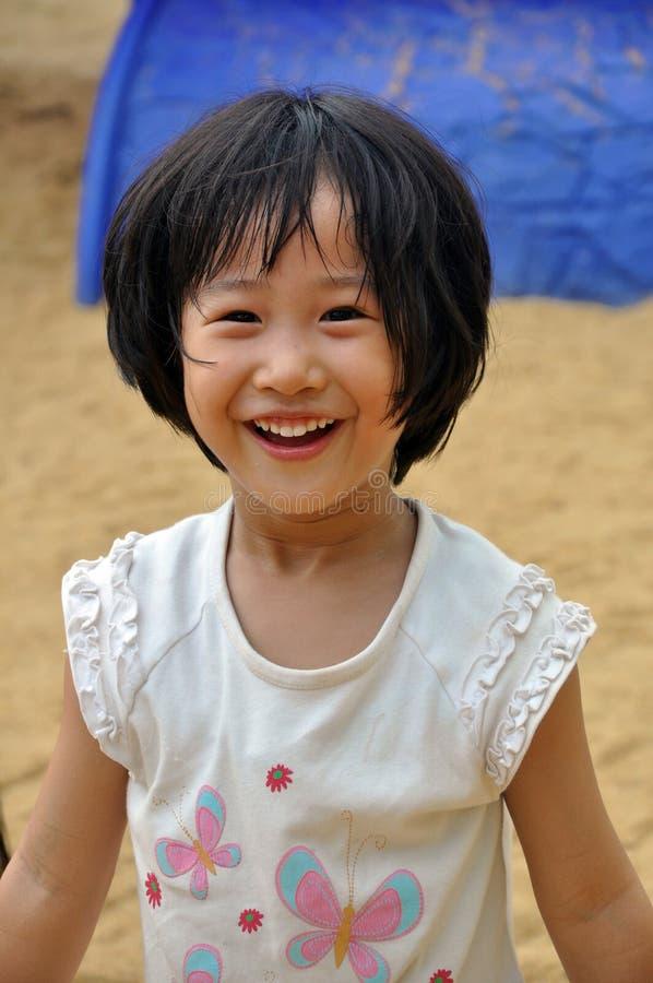 Z niewinnie wyrażeniem dzieciaka azjatycki uśmiech. zdjęcia stock