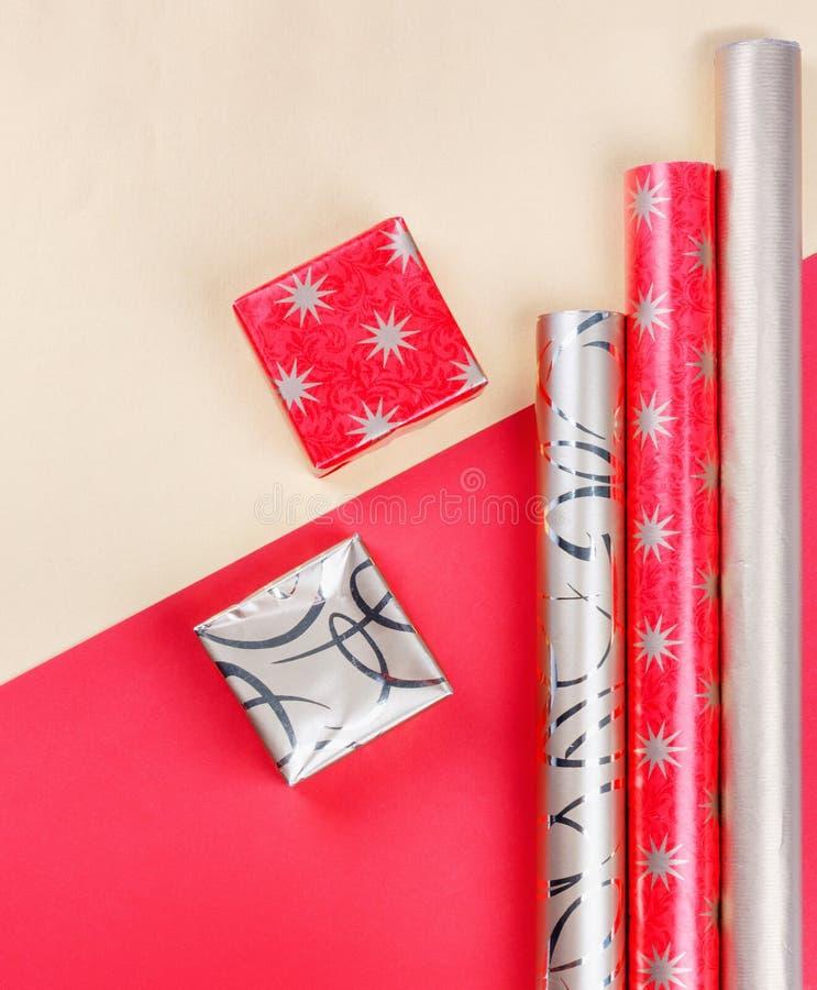 Z?oci prezent?w pude?ka i czerwony opakunkowy papier na jaskrawym tle obrazy stock