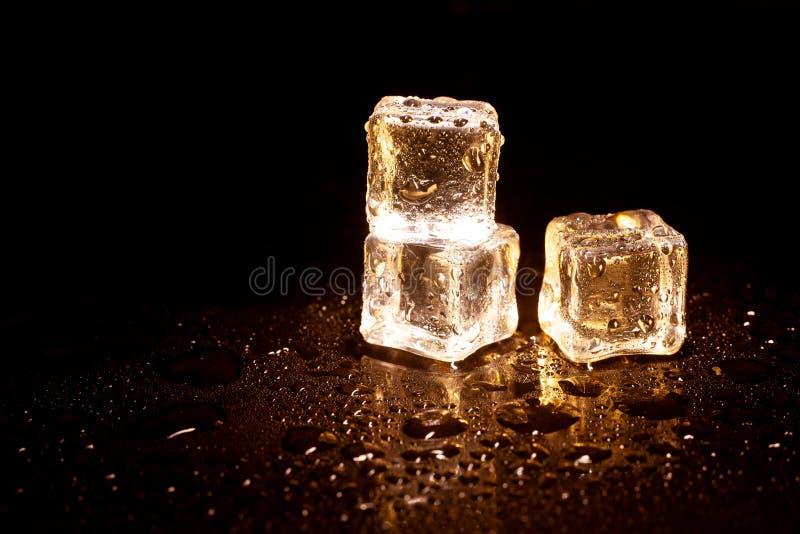 Z?ote kostki lodu na czarnym tle fotografia stock