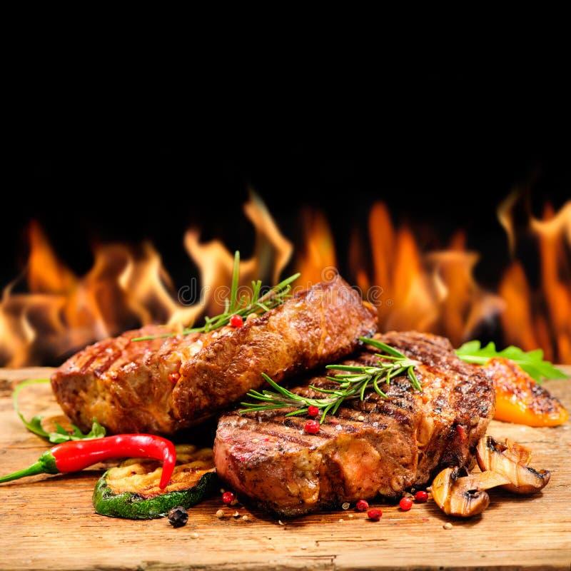 Z płomieniami wołowina piec na grillu stek obrazy stock