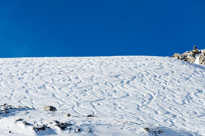 Z piste narciarskich śladów na prochowym śniegu obraz royalty free