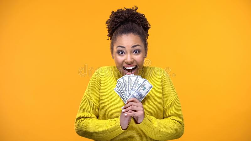 Z podnieceniem amerykanin kobieta trzyma wiązkę dolary, loteryjny zwycięzca, pomyślność obraz stock