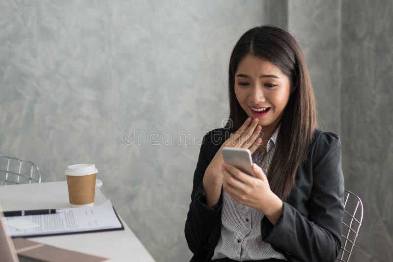 Z podnieceniem azjatykcia biznesowa dziewczyna podczas gdy czytający mądrze telefonu obsiadanie obraz royalty free