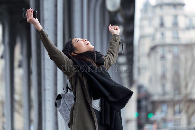 Z podnieceniem azjatykcia młoda kobieta świętuje sukces w ulicie zdjęcie royalty free