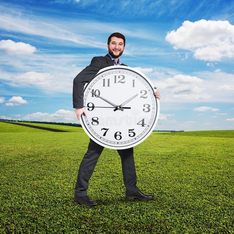 Z podnieceniem biznesmen trzyma dużego bielu zegar zdjęcie stock