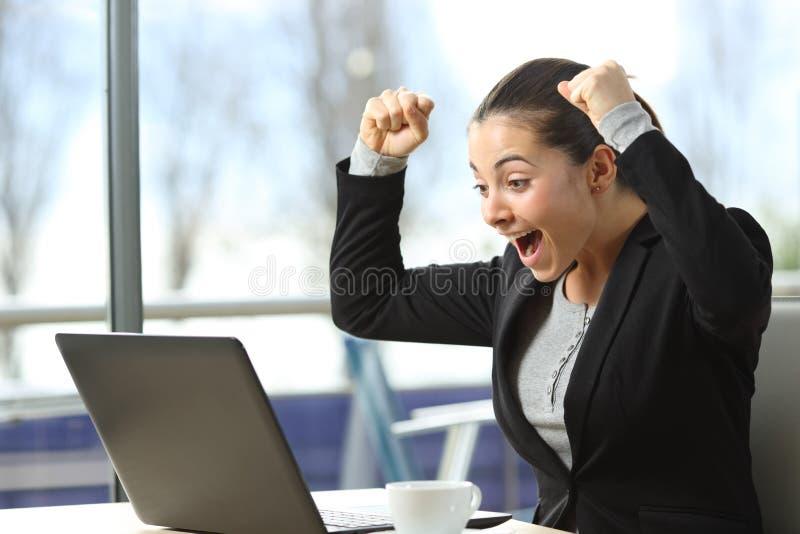 Z podnieceniem bizneswoman sprawdza laptop zawartość obrazy stock