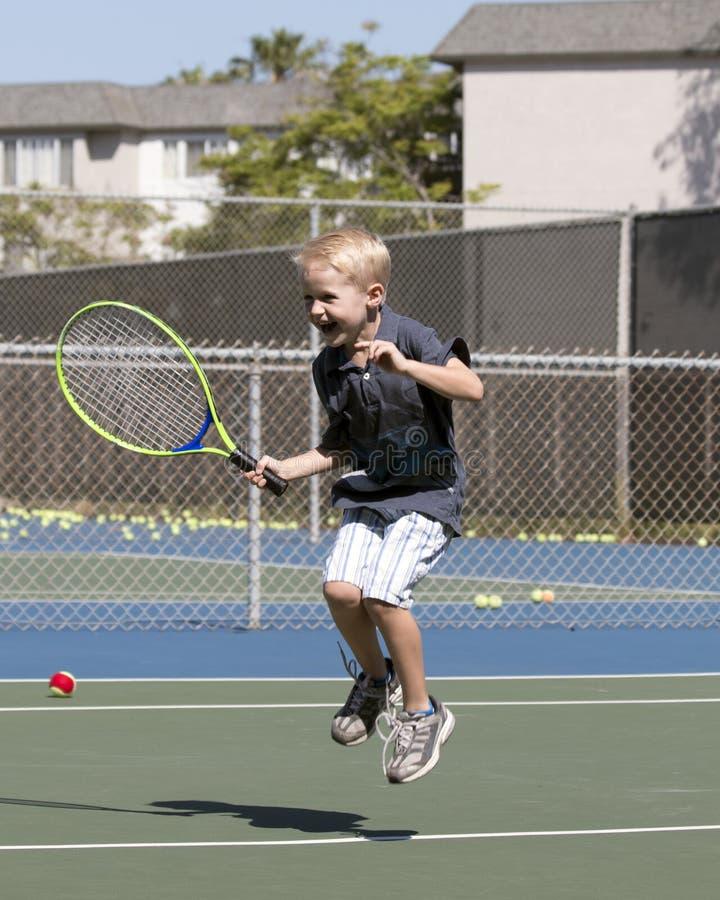 Z podnieceniem chłopiec bawić się tenisa zdjęcia royalty free