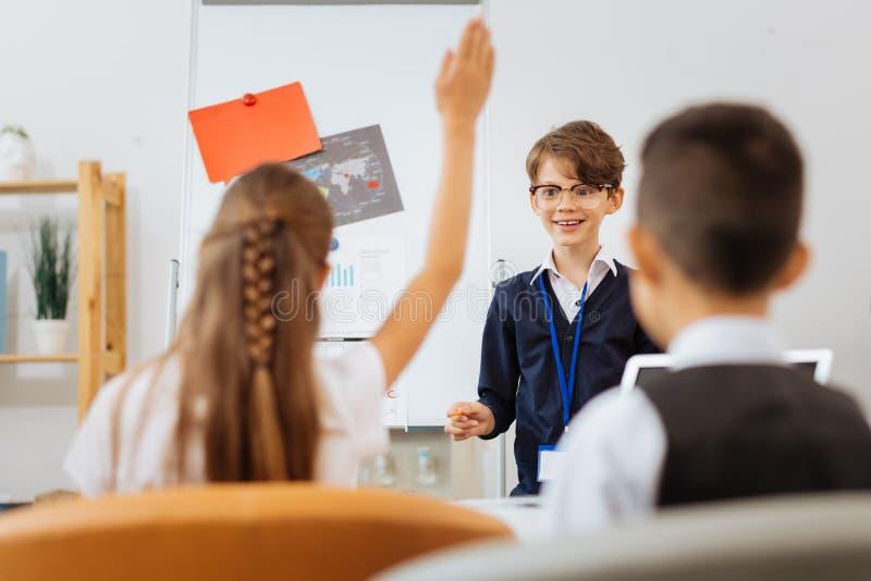 Z podnieceniem chłopiec pyta innych dzieci w szkłach zdjęcia royalty free