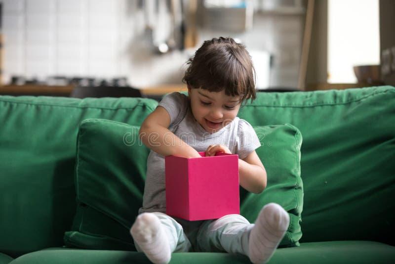 Z podnieceniem ciekawy małej dziewczynki otwarcie, sprawdza prezenta pudełko obrazy royalty free