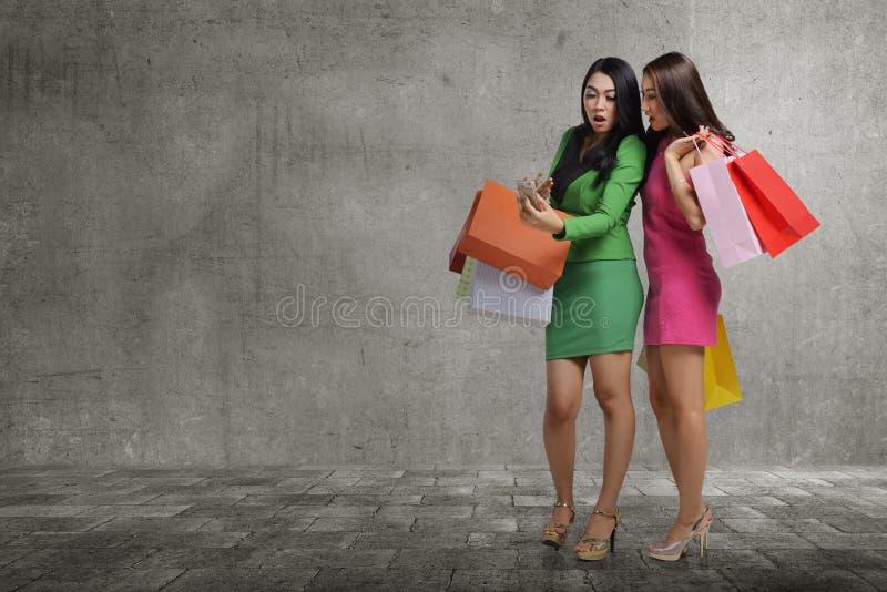 Z podnieceniem dwa azjatykciej kobiety patrzeje coś na telefonie komórkowym zdjęcie royalty free
