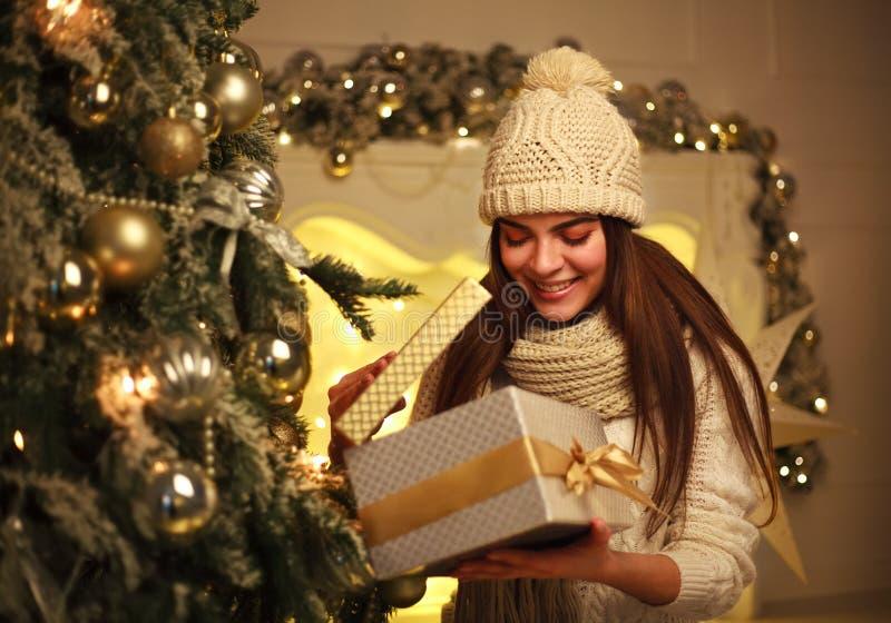 Z podnieceniem dziewczyna otwiera Bożenarodzeniowego prezent w nowego roku wystroju w domu obrazy stock