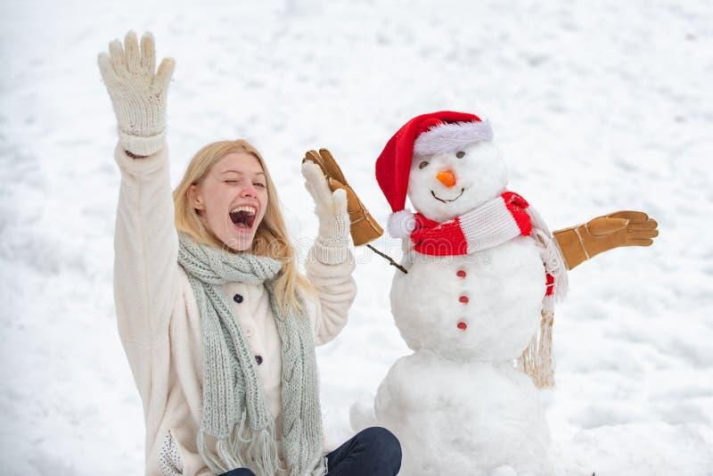 Z podnieceniem dziewczyna plaing z bałwanem na śnieżnym zima spacerze Robić bałwanu i zimy zabawy Śliczny bałwan w kapeluszu i sc zdjęcia stock