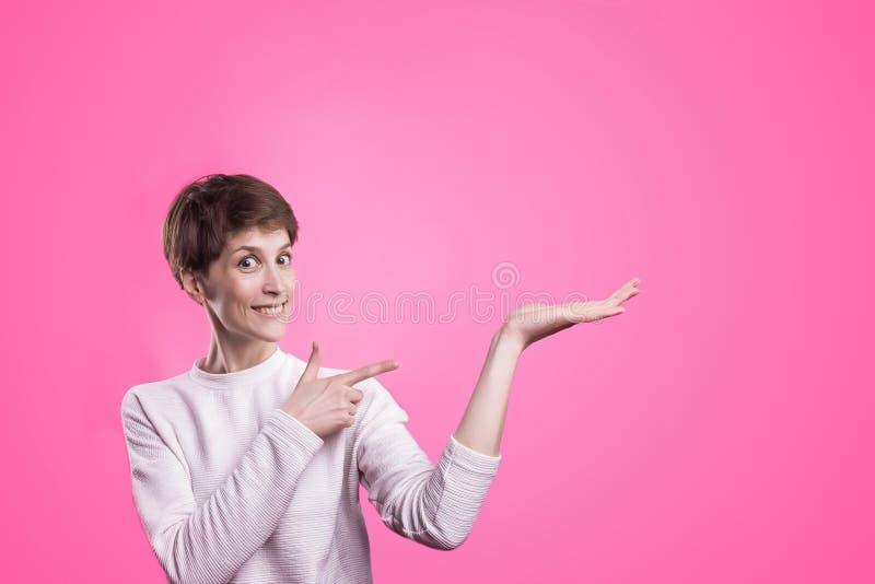 Z podnieceniem dziewczyna wskazuje pokazywać przy różowym tłem z kopii przestrzenią Młoda piękna szczęśliwa uśmiechnięta i roześm zdjęcie royalty free