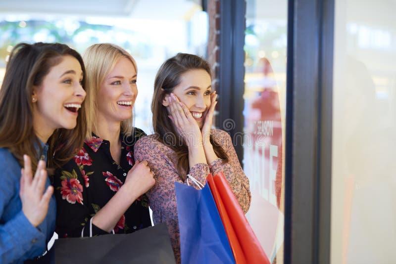 Z podnieceniem dziewczyny patrzeje sklepowego okno podczas dużego zakupy zdjęcie royalty free