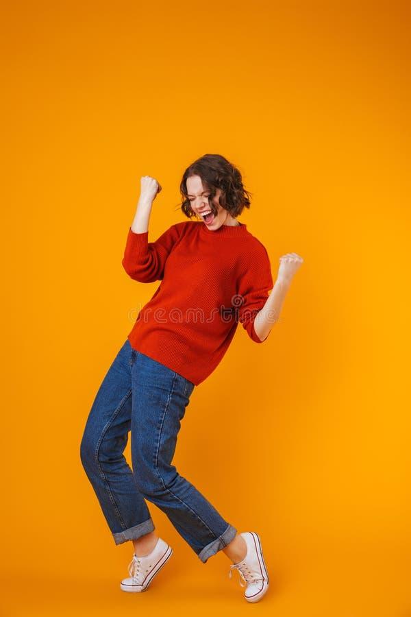 Z podnieceniem emocjonalny szczęśliwy młody ładny kobiety pozować odizolowywam nad kolor żółty ściany tłem zdjęcie stock