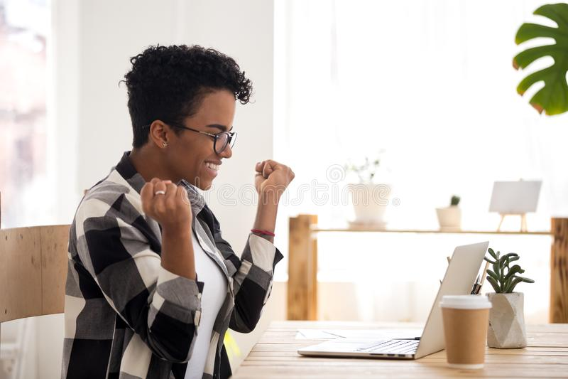 Z podnieceniem kobieta czuje szczęśliwego obsiadanie przy biurkiem indoors zdjęcia stock