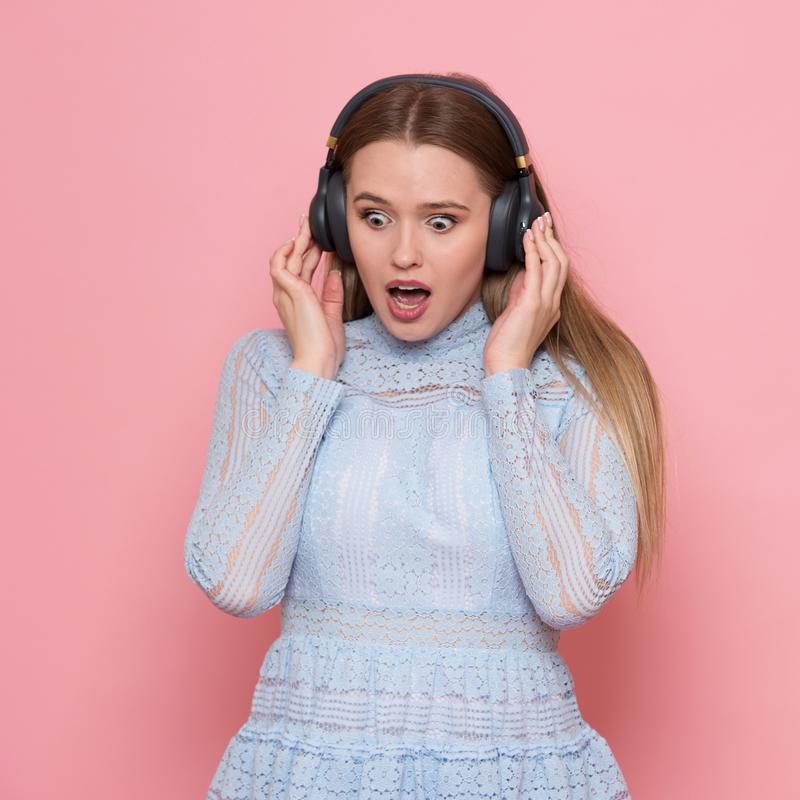 Z podnieceniem kobieta taniec i słucha muzyka jest ubranym hełmofony w menchii ścianie fotografia royalty free