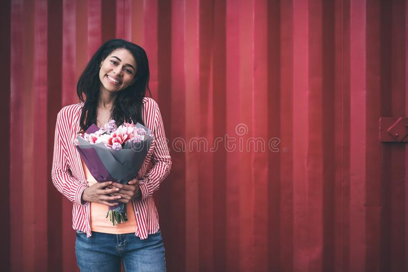 Z podnieceniem kobieta trzyma uroczych kwiaty i ono uśmiecha się szczęśliwie zdjęcia royalty free
