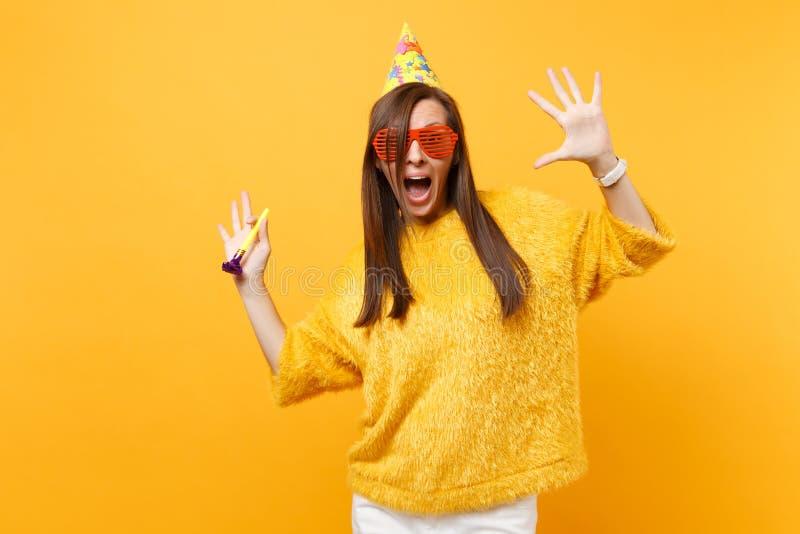 Z podnieceniem kobieta w pomarańczowych śmiesznych szkieł urodzinowym kapeluszu z bawić się fajczane podesłanie ręki, odświętność obraz royalty free