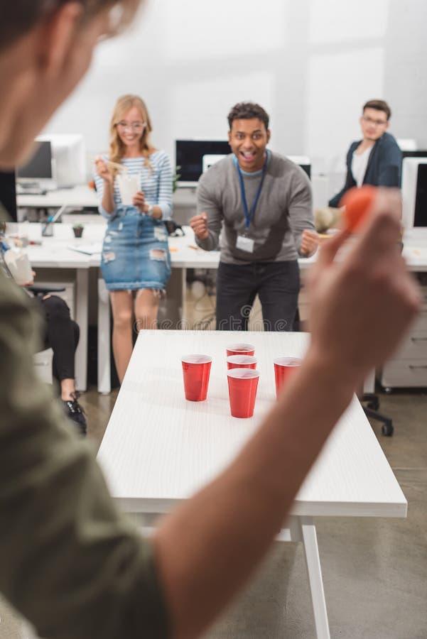 z podnieceniem ludzie bawić się piwnego pong przy nowożytnym biurem zdjęcia stock