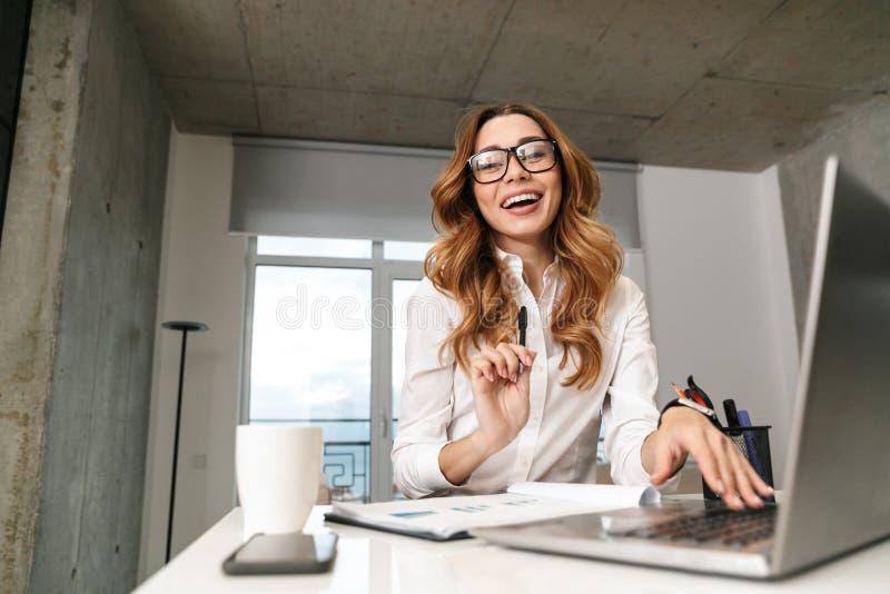 Z podnieceniem młoda biznesowa kobieta ubierał w formalnej odzieżowej koszula indoors używa laptop obrazy stock