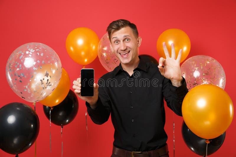 Z podnieceniem młody człowiek w czarnym klasycznym koszulowym mienie telefonie komórkowym z pustego czerni pustym ekranem pokazuj fotografia royalty free