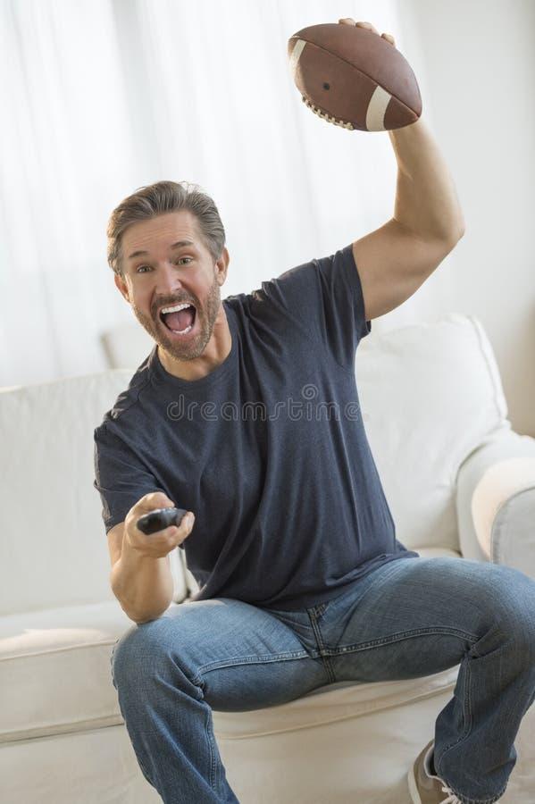Z podnieceniem mężczyzna dopatrywania futbolu amerykańskiego dopasowanie Na kanapie zdjęcia royalty free