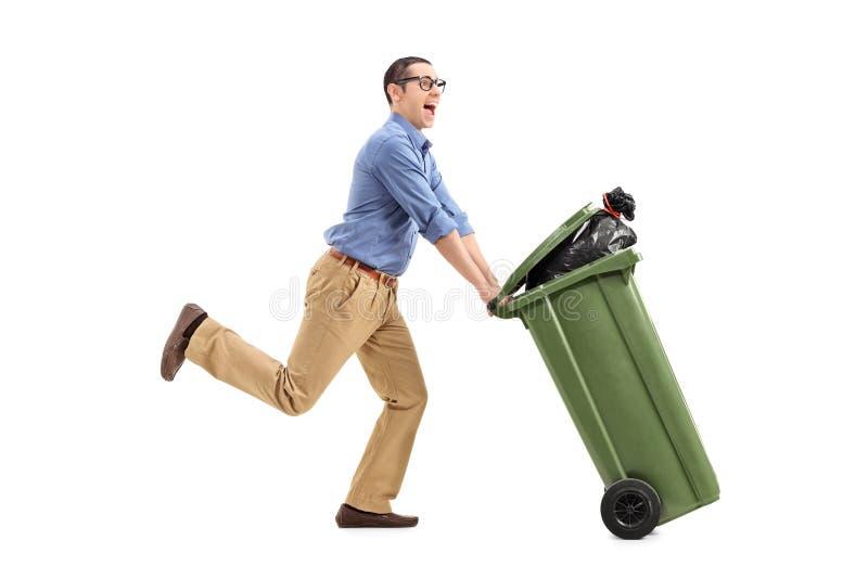 Z podnieceniem mężczyzna pcha pojemnik na śmiecie obraz stock