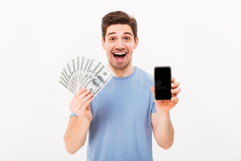 Z podnieceniem mężczyzna trzyma udziały pieniądze w dolarowym cu w przypadkowej koszulce fotografia royalty free