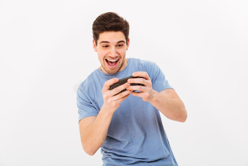 Z podnieceniem mężczyzna w przypadkowej koszulce bawić się gry online na smartphone obraz stock