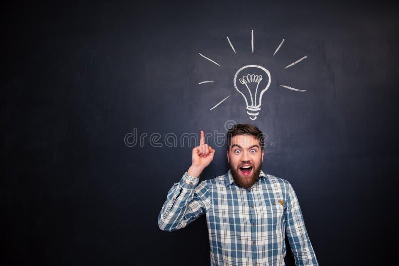 Z podnieceniem mężczyzna wskazuje up nad blackboard tłem z żarówką fotografia royalty free