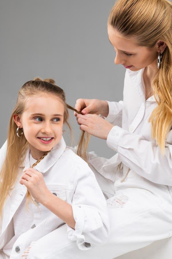 Z podnieceniem młoda dama opowiada jej stara siostra w białej kurtce zdjęcie stock